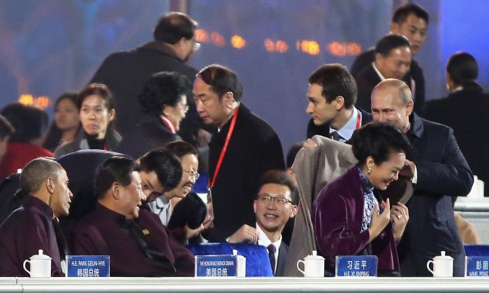 Nov. 10:  Russian President Vladimir Putin (R) puts on a shawl for Chinese President Xi Jinping's wife Peng Liyuan (2nd R) while Chinese President Xi Jinping (2nd L) and U.S. President Barack Obama (L) looks them before a fireworks show after the Welcome Banquet for 2014 APEC leaders (Feng Li/Getty Images)