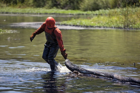 A Mexican state-owned petroleum company Pemex's worker cleans the San Juan river after an oil spill caused by a clandestine taking in a pipeline in San Juan Cadereyta, Nuevo Leon state, Mexico, on August 23, 2014. (Julio Cesar Aguilar/AFP/Getty Images)