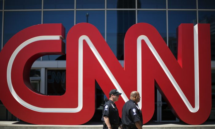 Security guards walk past the entrance to CNN headquarters in Atlanta. (AP Photo/David Goldman, File)