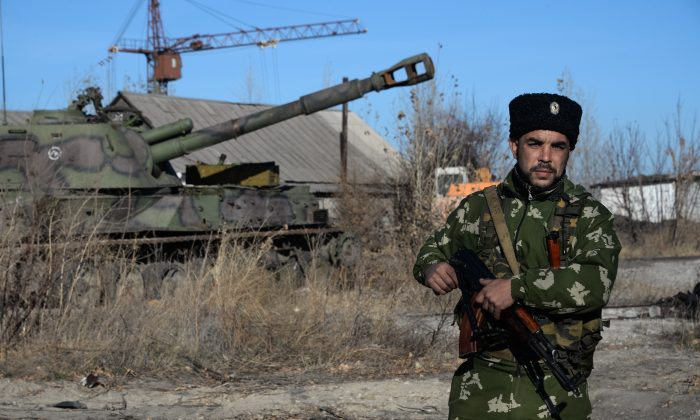 A Russian Cossack stands on guard at the military base in Perevalsk, Eastern Ukraine, Wednesday Nov. 5, 2014. Perevalsk and Alchevsk both participated in a contentious vote in early November to elect separatist deputies and leaders, but it is evident the outcome of the poll means little on the ground. (AP Photo/Mstyslav Chernov)