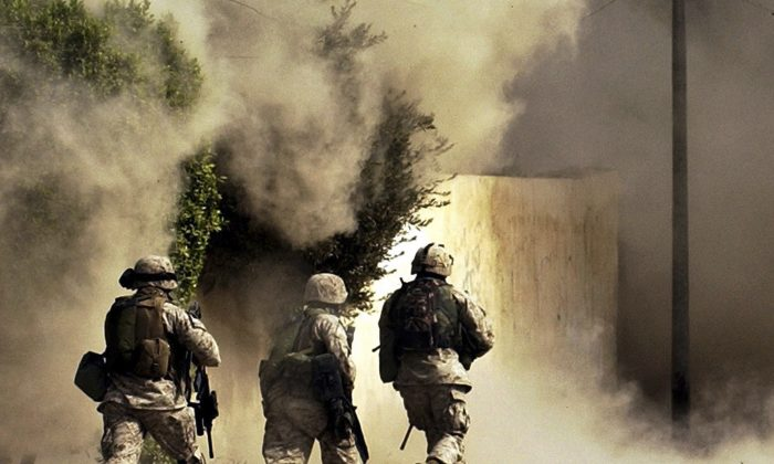 US Marines from the 2nd Battalion, 5th Marine Regiment, run to a building after detonating explosives to open a gate during a mission in Ramadi in Anbar province, Iraq, on Oct. 26, 2004.  (AP Photo/Jim MacMillan)