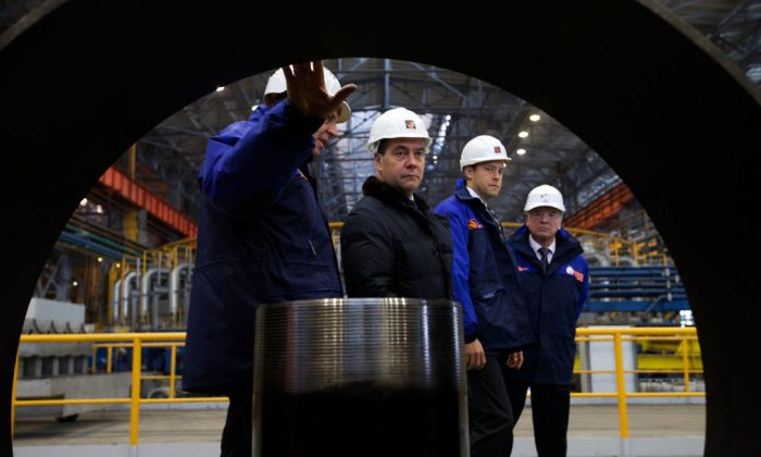 Russian Prime Minister Dmitry Medvedev (2L) accompanied by Dmitry Pumpyansky (L) head of TMK, Russia's largest maker of steel pipes for the oil and gas industry, visit the Seversky Tube Works in the town of Polevskoy, outside Yekaterinburg, Urals, on Oct. 24, 2014. (Ivan Sekretarev/AFP/Getty Images)