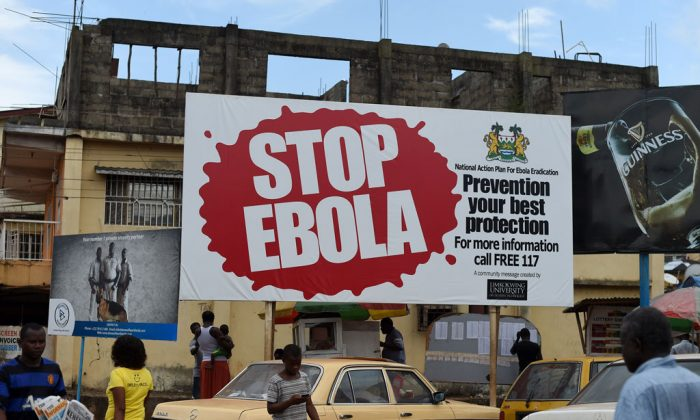 People walk past a billboard with a message about ebola in Freetown, Sierra Leone, on Nov. 7, 2014. (Francisco Leong/AFP/Getty Images)