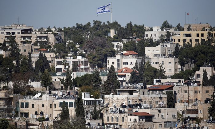 A giant Israeli flag flies over the Palestinian neighbourhood of Wadi Joz in East Jerusalem on Nov. 11, 2014. (Thomas Coex/AFP/Getty Images)