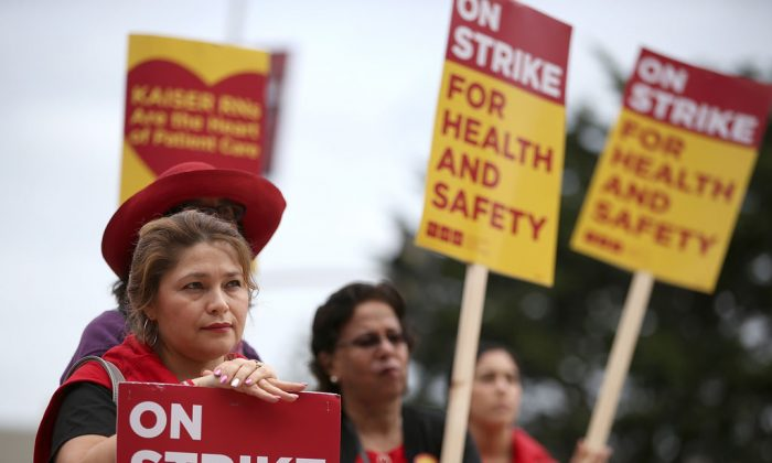 Nurses carry signs as they strike outside of Kaiser Permanente hospital on Nov. 11, 2014, in San Francisco, California. Nearly 18,000 Kaiser Permanente nurses in Northern California are staging a two-day strike amidst contract negotiations and to demand better working conditions, training and optimal safeguards for treating ebola. (Justin Sullivan/Getty Images)
