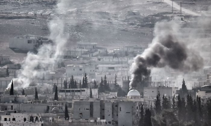 Smoke rises after the shelling of the city of Kobani, also known as Ain al-Arab, as it seen from the Turkish border village of Mursitpinar, Sanliurfa province, on Nov. 12, 2014. (Aris Messinis/AFP/Getty Images)