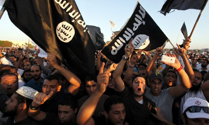 In this Sept. 21, 2012 file photo, Libyan followers of Ansar al-Shariah Brigades and other Islamic militias, hold a demonstration against a film and a cartoon denigrating the Prophet Muhammad in Benghazi, Libya.   (AP Photo/Mohammad Hannon, File)