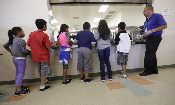 Detained immigrant children line up in the cafeteria at the Karnes County Residential Center, a temporary home for immigrant women and children detained at the border in Karnes City, Texas, on Sept. 10, 2014. (AP Photo/Eric Gay)