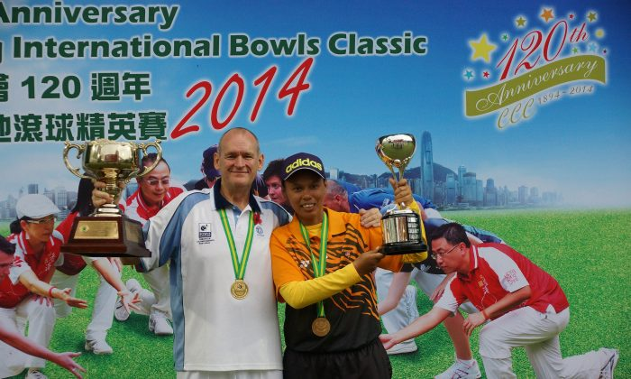 WE ARE THE CHAMPION—Scottish bowler Robert Grant (left) and Siti Zalina Ahmad from Malaysia proudly display their Hong Kong International Bowls Classic singles trophies on Sunday Nov 9, 2014. (Mike Worth)