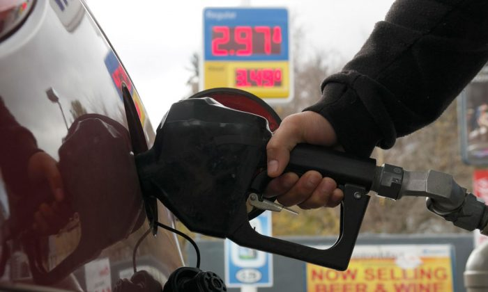 A motorist refuels at a gas station where prices have dipped below $3 per gallon, Monday, Oct. 27, 2014, in Pittsfield, Mass. A national survey of gas prices reports that the average cost of US regular grade gas dropped 18 cents per gallon in the last two weeks. (AP Photo/The Berkshire Eagle, Ben Garver)