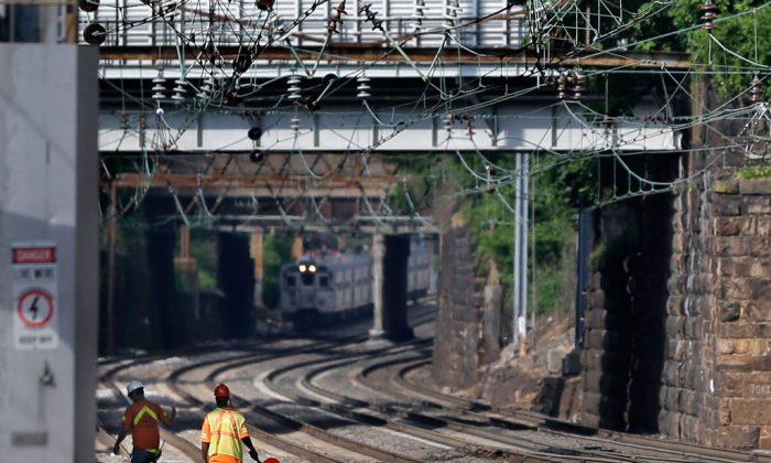 Workers walk along the tracks as a New Jersey Transit train pulls into the Trenton train station in Trenton, N.J., on July 8, 2014. (AP Photo/Mel Evans)