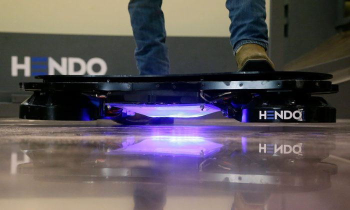 Arx Pax engineer Garrett Foshay stands over a Hendo Hoverboard in Los Gatos, Calif., on Oct. 30, 2014. Skateboarding is going airborne this fall with the launch of the first real commercially marketed hoverboard which uses magnetics to float about an inch off the ground. (AP Photo/Jeff Chiu)