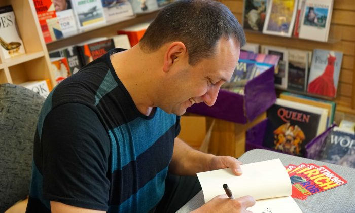 "Toronto author Rob Brunet signs a copy of his first novel ""Stinking Rich"" at Perfect Books in Ottawa on Nov. 2, 2014. (Pam McLennan/Epoch Times)"