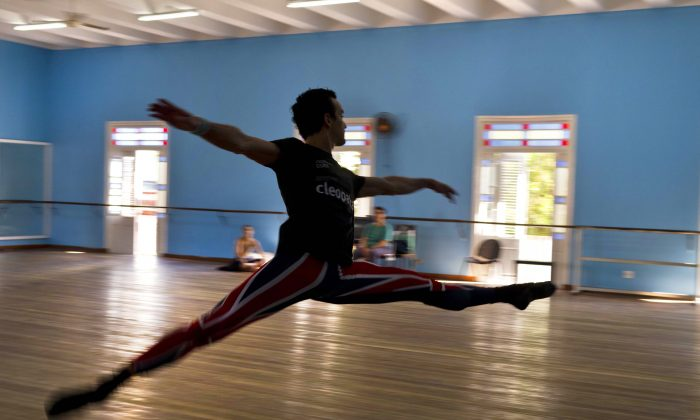 """In this Oct. 29, 2014 photo, Cuban dancer Javier Torres practices at the National Cuban Ballet dance house in Havana, Cuba. Torres, a star dancer with the Northern Ballet of Great Britain, said the spirit of their homeland shapes their art no matter how far they travel. """"We are Cubans and we carry the Cuban interpretation of ballet _ what we have learned here,"""" he said. Torres was among a dozen Cuban dancers who returned to the island to be part of the 24th International Ballet Festival of Havana. (AP Photo/Franklin Reyes)"""