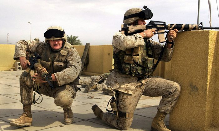 US Marine snipers from the 2nd Battalion, 5th Marine Regiment, take cover during a gun battle with insurgents in Ramadi in Anbar province, Iraq, on Oct. 31, 2004. (AP Photo/Jim MacMillan)