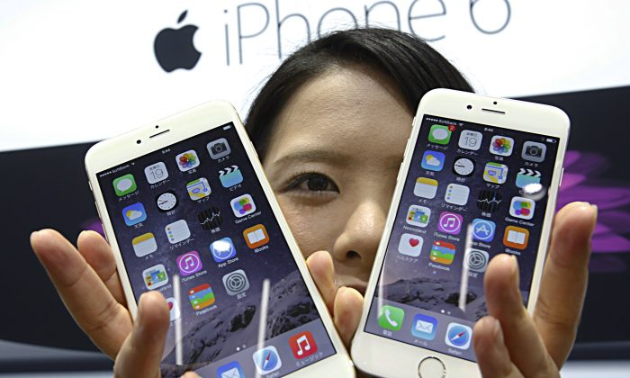 A customer shows off the new Apple iPhone 6 and 6 Plus at a store in Tokyo Friday, Sept. 19, 2014. (Shizuo Kambayashi/AP Photo)
