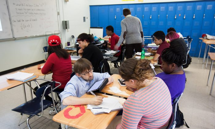 Two teachers help students in a classroom at the MESA Charter High School in Bushwick, Brooklyn, New York, on Oct. 28, 2014. (Petr Svab/Epoch Times)