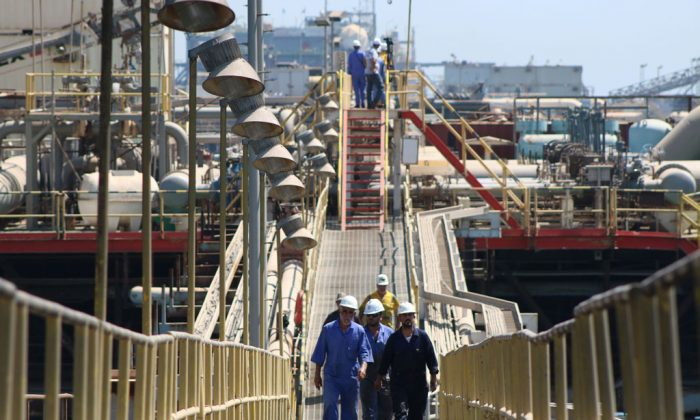 Iraqi labourers walk past an oil tanker docked at a floating platform on Sept. 21, 2014, offshore from the southern Iraqi port city of Al Faw, 90 kilometres south of Basra. (Haidar Mohammed Ali/AFP/Getty Images)