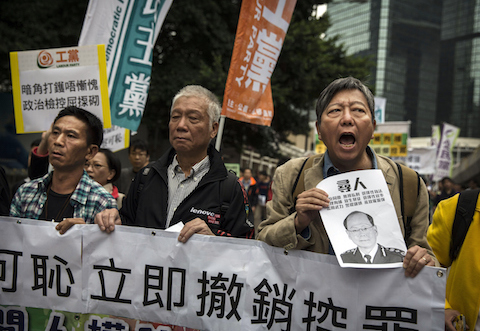 Pro-democracy demonstrators chant as they march during a demonstration against the arrest of protest marshalls by police the night before, at the Admiralty protest site on November 13, 2014 in Hong Kong, Hong Kong. Hong Kong's high court has authorized police to arrest protesters who obstruct bailiffs on the three interim restraining orders.  (Photo by Kevin Frayer/Getty Images)