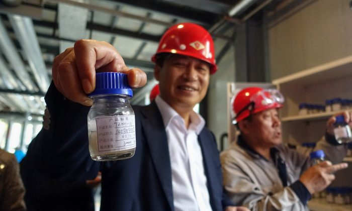 Tianhe Chief Executive Wei Xuan shows journalists a sample of one of the specialty chemicals the company manufactures at its 800,000 square meter Jinzhou plant in China on Oct. 24, 2014. The pitch to investors described the company on the verge of spectacular success. Tianhe Chemicals Group Ltd. boasted rock-bottom labor costs, unique manufacturing techniques and net profit margins triple those of competitors. (AP Photo/Erika Kinetz)