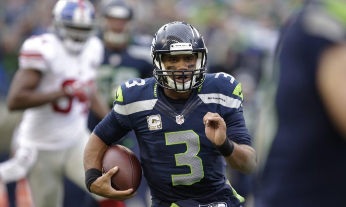 Seattle Seahawks quarterback Russell Wilson runs with the ball against the New York Giants in the first half of an NFL football game, Sunday, Nov. 9, 2014, in Seattle. (AP Photo/Scott Eklund)