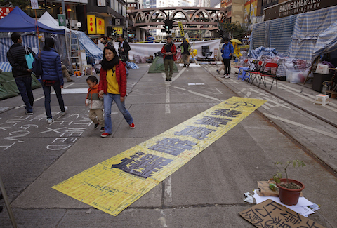 "The yellow banner reads "" I want genuine universal suffrage."" is displayed by protesters in the Causeway Bay shopping district, one of the occupied areas in Hong Kong Saturday, Dec.13, 2014. (AP Photo/Kin Cheung)"