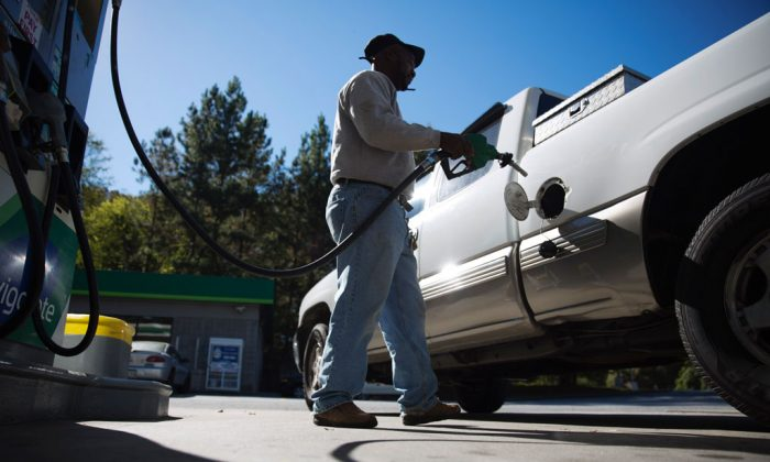Motorist Jerry Reed fills up his tank at a gas station in Atlanta on Oct. 30, 2014. Almost unbelievably, the national average price of a gallon of gasoline is back under $3 for the first time since Dec. 2010. (AP Photo/David Goldman)