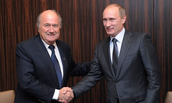 Russian Prime Minister Vladimir Putin (R) shakes hands with FIFA President Joseph Blatter after Russia was announced as the host for the 2018 soccer World Cup in Zurich, Switzerland. (AP Photo/Kurt Schorrer)