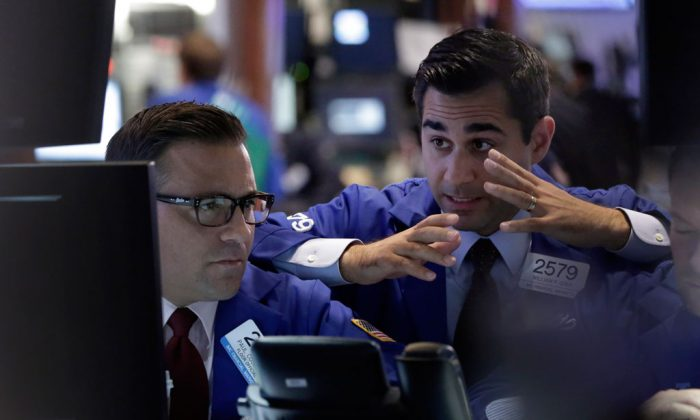 Specialists Paul Cosentino (L) and William Geer work at a post on the floor of the New York Stock Exchange, Thursday, Oct. 16, 2014. US stocks drifted between small gains and losses in late afternoon trading Thursday, struggling to remain in positive territory after a steep slide early in the day. (AP Photo/Richard Drew)