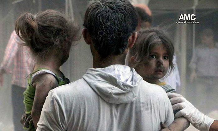 A Syrian man helping children out of a damaged building following a Syrian government airstrike in the Shaar neighborhood of Aleppo, Syria, on July 9, 2014. Despite being battered by a war, now in its fourth year, the country is still firmly under the grip of President Bashar Assad despite an armed rebellion to uproot him and losing territory to opposition rebels and the extremist Islamic State group. (AP Photo/Aleppo Media Center-AMC)