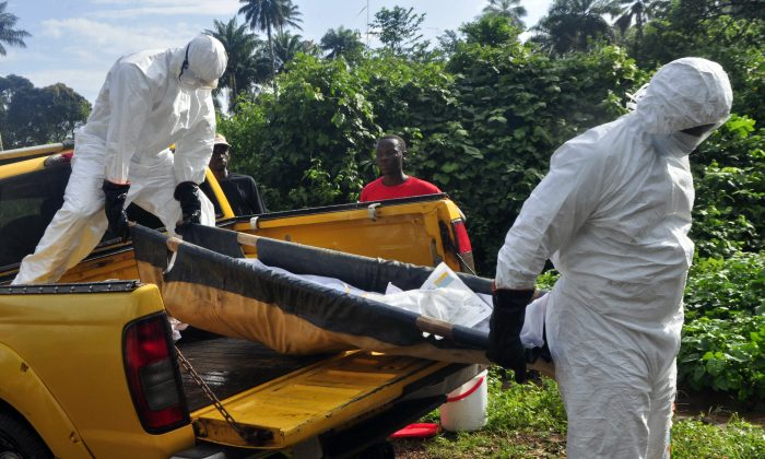 Health workers unload the lifeless body of a man suspected of contracting the Ebola virus, as they carry him to a grave site on the outskirts of Monrovia, Liberia, on Oct. 27, 2014. Health officials in the US and Europe are scrambling to begin testing a handful of experimental Ebola drugs in Africa, but an ethical debate is brewing over how to appropriately test medicines amid an outbreak that has already killed nearly 5,000 people. (AP Photo/Abbas Dulleh)
