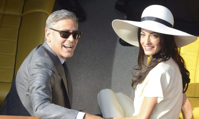 George Clooney and his wife, human rights lawyer Amal Alamuddin, after their marriage ceremony in Venice, Italy, on Sept. 29, 2014. (AP Photo/Luigi Costantini)