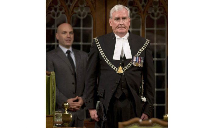 NDP MP Nathan Cullen (L) looks on as sergeant-at-arms Kevin Vickers gets a long standing ovation in the House of Commons on Oct. 23, 2014. Hailed as a hero at home, Vickers is now getting a celebrity welcome abroad. (The Canadian Press/Adrian Wyld)