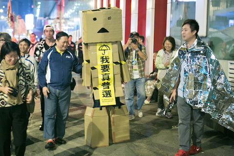 "A person dressed inside cardboard boxes walks around in the Mong Kok protest site with a the main banner that reads ""We want universal suffrage,"" in Hong Kong on Nov. 13, 2014. (Benjamin Chasteen/Epoch Times)"