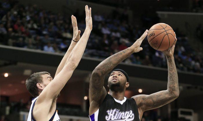 Sacramento Kings center DeMarcus Cousins (15) shoots against Memphis Grizzlies center Marc Gasol in the first half of an NBA basketball game Thursday, Nov. 13, 2014, in Memphis, Tenn. (AP Photo/Mark Humphrey)
