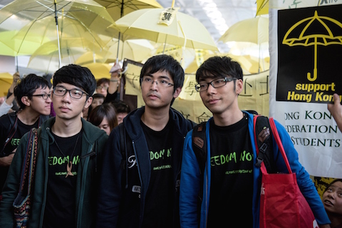 Student leaders Alex Chow (C), Nathan Law (L) and Eason Chung (R) are surrounded by pro-democracy protesters at the Hong Kong international airport before their scheduled flight to Beijing on November 15, 2014. Pro-democracy protest leaders say they will head to Beijing in hopes of bringing their demands for political reform to Chinese authorities. (Alex Ogle/AFP/Getty Images)