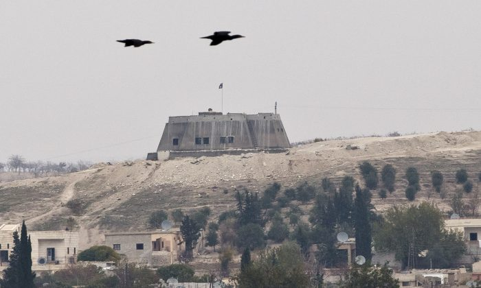 Birds fly backdropped by an building with the Islamic State group flag on top, in the Syrian city of Jarablous, seen from an archaeologic site outside Karkemish, Turkey, Saturday, Nov. 15, 2014. Archaeology and war don't usually mix, yet that's been the case for years at Karkemish, an ancient city along the Turkey-Syria border where an excavation team announced its newest finds Saturday just meters from Islamic State group-controlled territory. (AP Photo/Vadim Ghirda)