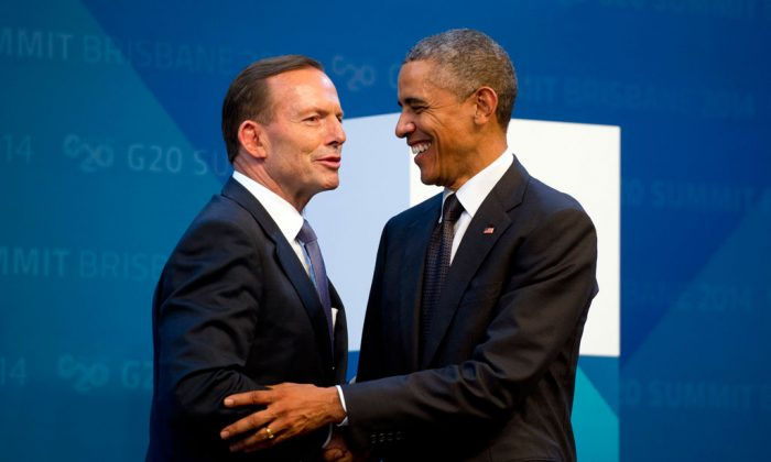 US President Barack Obama (R) is welcomed by Australia's Prime Minister Tony Abbott upon arrival for the G20 Summit in Brisbane, Australia, Saturday, Nov. 15, 2014. (AP Photo/Alain Jocard)