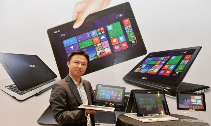 Peter Chang, Head of South Asia and Country Manager - System Business Group of ASUS India, showcases the company's Transformer Series of laptop/netbook/tablet combination during its launch in Bangalore on Nov. 14, 2014. (Manjunath Kiran/AFP/Getty Images)
