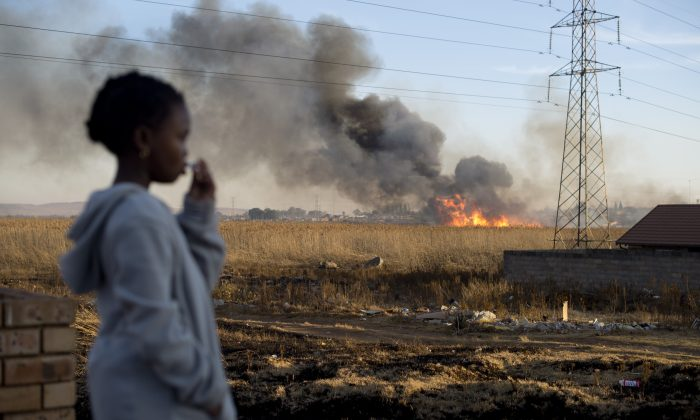 A girl looks at a fire in the township of Soweto on June 27, 2013. (Odd Andersen/AFP/Getty Images)
