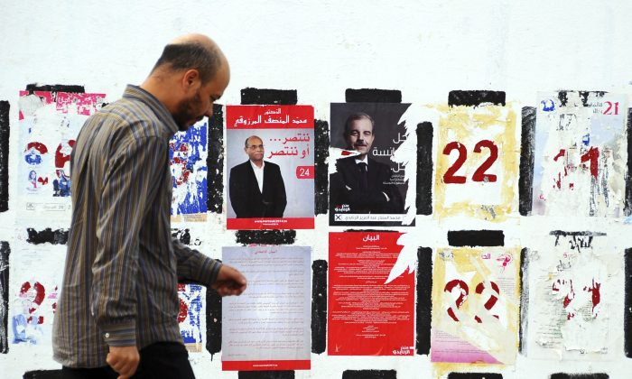 A man walks past electoral posters for the upcoming presidential elections in Tunis on Nov. 5, 2014. Campaign posters and banners for next week's presidential elections have covered the walls of Tunisia's cities and towns, papering over the flaking posters from the parliamentary elections just three weeks ago. (AP Photo/Hassene Dridi)