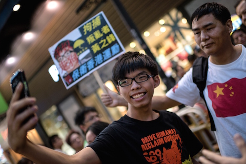 """Hong Kong student leader Joshua Wong (C) takes a """"selfie"""" next to a pro-Beijing activist (R) who had been shouting slogans at Wong as he handed out flyers in support of the Hong Kong pro-democracy protests, in the Causeway Bay area of Hong Kong on November 16, 2014.  Three Hong Kong democracy protest leaders were on November 15 denied permission to board a flight to Beijing, where they had hoped to bring their demand for free elections directly to Chinese authorities. Protesters have been occupying key intersections around the former British colony calling for fully free leadership elections in 2017, but Beijing has insisted that all candidates be screened by a loyalist committee.  (Alex Ogle/AFP/Getty Images)"""