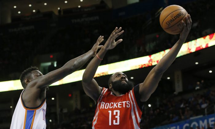Houston Rockets' James Harden (13) shoots in front of Oklahoma City Thunder's Anthony Morrow, left, in the second quarter of an NBA basketball game in Oklahoma City, Sunday, Nov. 16, 2014. (AP Photo/Sue Ogrocki)