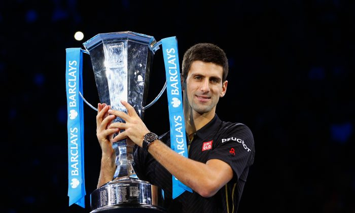 Image Caption: Novak Djokovic of Serbia poses with the ATP trophy on day eight of the Barclays ATP World Tour Finals at O2 Arena on November 16, 2014 in London, England. (Julian Finney/Getty Images)