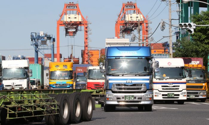 Trucks leave a container wharf in Tokyo on Sept. 26, 2014. Japan reported Monday, Nov. 17, that its economy contracted at a real annual rate of 1.6 percent in July-September in the second straight quarterly decline. Most economists had forecast the world's third-biggest economy expanded at about a 2 percent pace. The negative growth figure was much lower than expected and makes it very likely Prime Minister Shinzo Abe will delay implementation of a sales tax hike planned for October 2015. (AP Photo/Koji Sasahara)