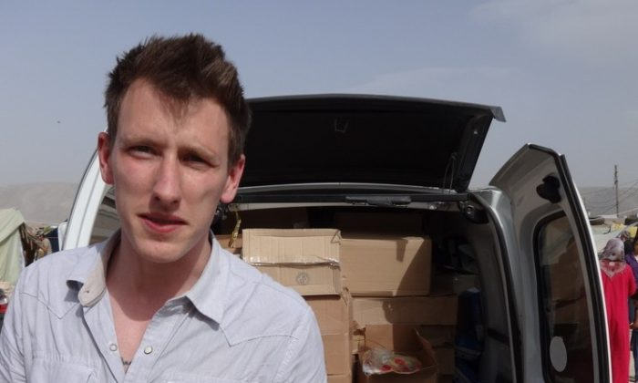 Peter Kassig stands in front of a truck filled with supplies for Syrian refugees in this undated photo provided by his family. A new graphic video purportedly produced by Islamic State militants in Syria released Sunday, Nov. 16, 2014 claims U.S. aid worker Kassig was beheaded. (AP Photo/Courtesy Kassig Family)