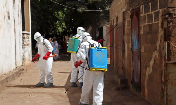 Health workers spray disinfectant around a mosque after the body of a man suspected of dying from the Ebola virus was washed inside before being berried in Bamako, Mali, on Nov. 14, 2014. It all started with a sick nurse, whose positive test results for Ebola came only after death. In a busy clinic that treats Bamako's elite as well as wounded UN peacekeepers, who was the patient who had transmitted the virus? Soon hospital officials were taking a second look at the case of a 70-year-old man brought to the capital late at night from Guinea suffering from kidney failure. On Friday, Malian health authorities went to disinfect the mosque where the 70-year-old's body was prepared for burial - nearly three weeks ago. Already some are criticizing the government for being too slow to react when health authorities had announced his death as a suspected Ebola case earlier in the week. (AP Photo/Baba Ahmed)