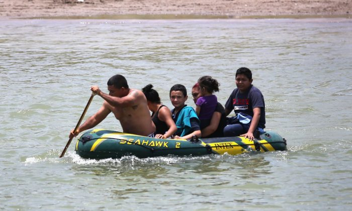 A suspected smuggler brings alleged illegal Salvadoran immigrants, most of them minors, across the Rio Grande from Mexico into the United States in Mission, Texas, on July 24, 2014. (John Moore/Getty Images)