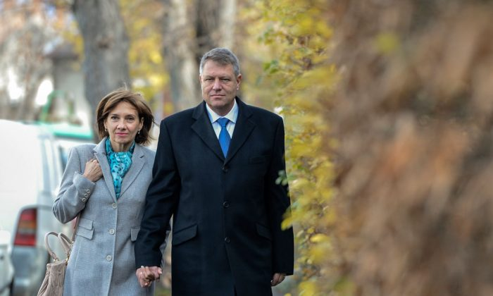 Klaus Iohannis, leader of Romania's center-right Liberals and mayor of the Transylvanian city of Sibiu, holds his wife Carmen's hand while walking to a polling station in Sibiu, in the central Romanian Transylvania region, Sunday, Nov. 16, 2014. Romanians have begun voting in a presidential runoff between the prime minister who promises stability and a city mayor who says he will fight corruption. The winner will replace President Traian Basescu, who steps down after 10 years. (AP Photo/Andreea Alexandru, Mediafax)