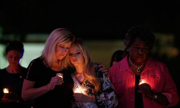 Elizabeth Jones (L) and her daughter Taylor Jones (R), 19, attend a candlelight vigil to support Domestic Violence Awareness Month in Montgomery, Ala., on Oct. 1, 2014. Taylor Jones said she was a victim of domestic violence when she was 15-years-old and now stands against domestic violence as an International Junior Miss Teen. Jones says that she started an organization called TIARA Charities (Teens In-action Against Relationship Abuse) in hopes to bring abuse awareness to her community. (AP Photo/Brynn Anderson)